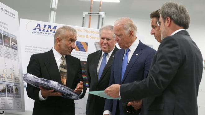 Dr. Alain Kaloyeros, founding President and CEO of SUNY Polytechnic Institute, left, and Michael Liehr, Executive Vice President of Innovation and Technology, Colleges of Nanoscale Science and Engineering, SUNY Polytechnic Institute, right, brief Vice President Joe Biden, center, New York Governor Andrew Cuomo, second from right, and Defense Department Under Secretary Frank Kendall, as they visit SUNY Poly Canal Ponds on Monday during the official announcement of the Department of Defense awarding $110 million to help create the American Institute for Manufacturing Integrated Photonics.
