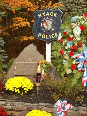 A memorial is decorated with flowers during the 31st annual Brinks robbery memorial ceremony in Nyack Oct. 20, 2012. ( Peter Carr / The Journal News )
