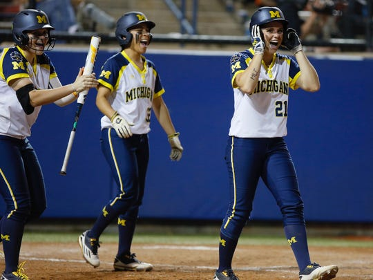 Michigan's Kelly Christner, at right, Sierra Romero, center, and Aidan Falk celebrate after Michigan scored two runs in the sixth inning of a softball game against LSU in the Women's College World Series between at ASA Hall of Fame Stadium in Oklahoma City, Friday, June 3, 2016.