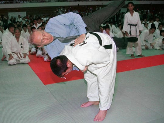 A Japanese judo student executes a flip on Russian