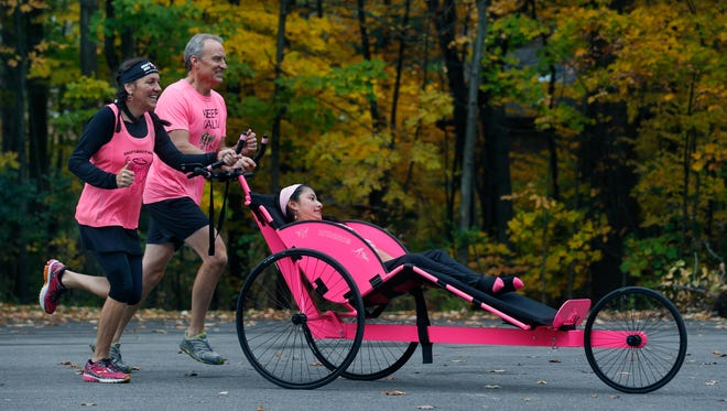 As team Hoyt, Onni Peck, 22, is pushed by friend Marie Boudreau-Ninkov of Brighton and by her father Michael for a final training run before Sunday's Marine Corps Marathon in D.C. Onni has a regressive neuromuscular illness which leaves her unable to walk. In this photo they run in Fairport past Onni's home.