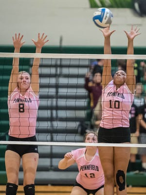 Pennfield's Lucy Webb (8) and Jaylyn Shepard (10) go for the block during Wednesday's game against Hastings.