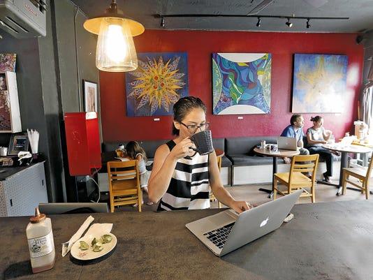 Ana Huesca enjoys a drink at Joe Vinny & Bronson's Bohemian Cafe while she works on Wednesday.