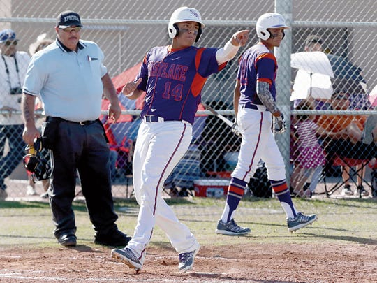 Eastlake's Alex Pinedo, 14, steps on home plate and points to teammate Arturo Sanchez, 18, who hit a base hit allowing the run to come in during a high school game played in 2015.