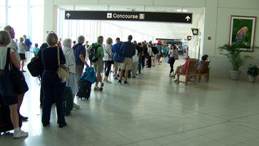Travelers queue up some 100 yards before Concourse B checkpoint at Southwest Florida International Airport on Wednesday, March 16, 2016.  March historically is the Fort Myers airport's busiest month.