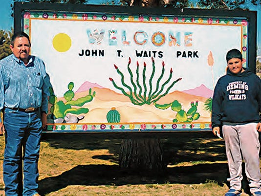Standing next to the sign that was designed and painted by local muralist Dina Marquez is Red Mountain Middle School shop teacher Jerry Montes and student Javier Hernandez.