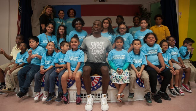 Lex Gillette, a blind Paralympian, poses for a group photo with Cooper's Poynt students during a surprise visit to the Camden school.