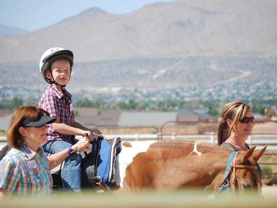 Six-year-old David Evans rides a therapy horse at Sierra