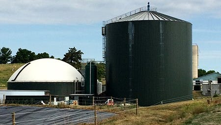 An anaerobic digester unit (left, with the white roof) on a dairy farm. The large facility to the right of it is a storage tank holding treated, digested manure that may later be applied to fields to fertilize crops.