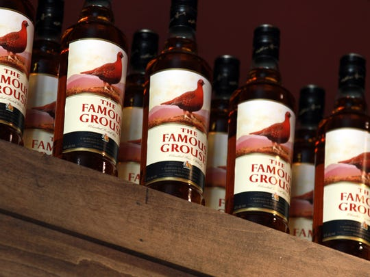 Bottles of The Famous Grouse scotch line a shelf Wednesday,