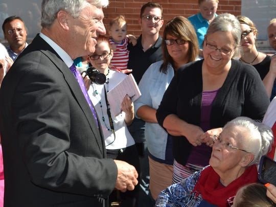 State Sen. Gerald Long speaks to Juanita McNeal (right) and her family at a ceremony honoring Juanita's late husband, James. James was inducted into the Legion of Honour, France's highest distinction, for his World War II service.