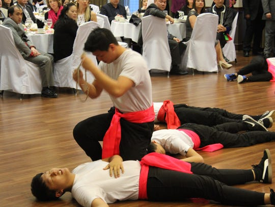 Members of a Wausau Hmong dance troupe, ReUnited, perform