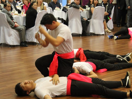 Members of a Wausau Hmong dance troupe, ReUnited, perform an interpretive dance. The dance began with a piece about the Hmong role during the Vietnam War.