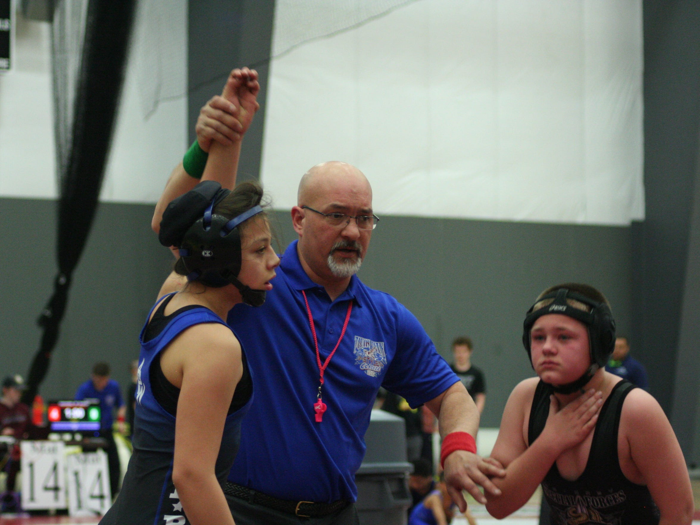 Destiny Rodriguez (left) of Keizer has her hand raised after defeating a boy in a wrestling tournament.
