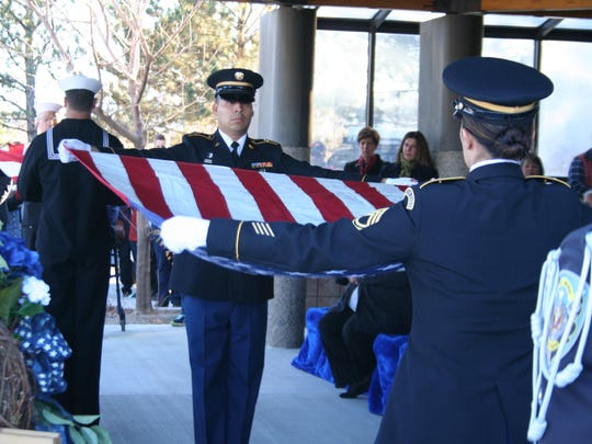 Military officers fold American flags and provide them