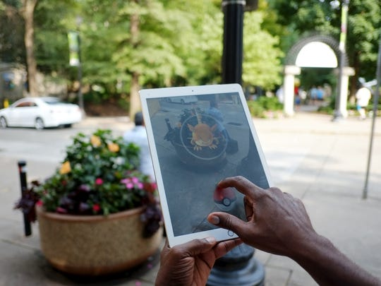 John Jackson catches a Raticate on his tablet in Market Square during the Facebook group, Knoxville Pokemon Go hunt event on Saturday, July 23, 2016.
