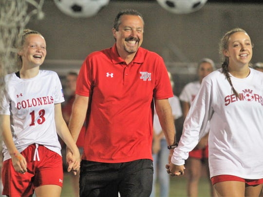 Dixie Heights head coach Chris Sturm, middle, with