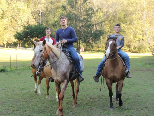 Lawson, Nathan and Trace Bates ride horses on an episode