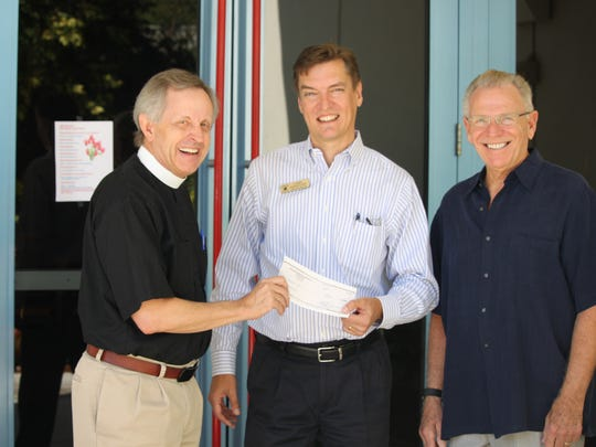 Iona Hope Episcopal's Father Ray Buchanan gives a check