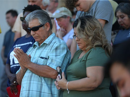 Attendees bow their heads to pray during a prayer vigil on the steps of the Tom Green County Courthouse for immigrant families who have been separated Monday, June 25, 2018.