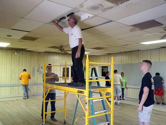 Volunteers look over the light fixtures at the Veterans