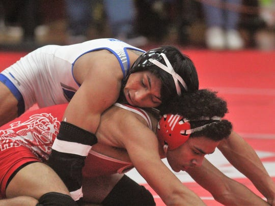 Covington Catholic senior Mannie Murrer, top, wrestles