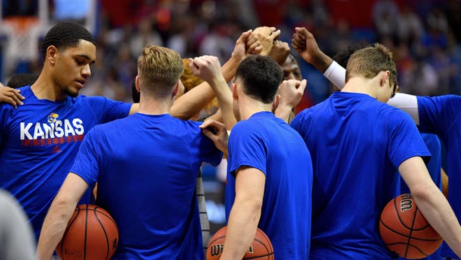 Kansas basketball's Tristan Enaruna, left, and teammates huddle up before a game against East Tennessee State last year at Allen Fieldhouse in Lawrence. The Jayhawks will play nine nonconference games this season.