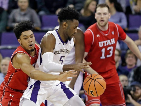 Washington's Jaylen Nowell (5) tries to hold on to the ball as Utah's Sedrick Barefield, left, reaches for it and David Collette (13) watches during the second half of an NCAA college basketball game Thursday, Feb. 15, 2018, in Seattle. Utah won 70-58. (AP Photo/Elaine Thompson)