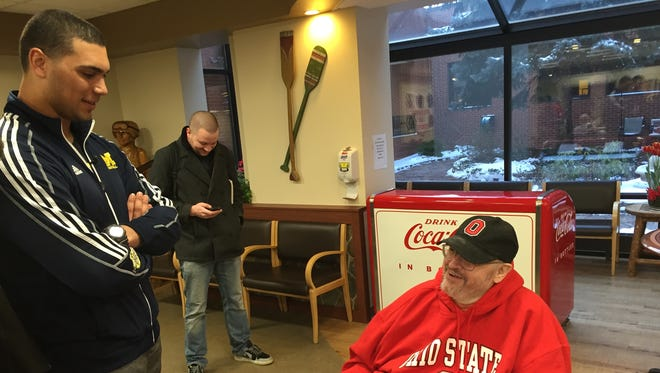 Michigan defensive lineman Chris Wormley talks to veteran Alan Williams, sporting an Ohio State sweatshirt and hat, at Ann Arbor's VA Hospital.