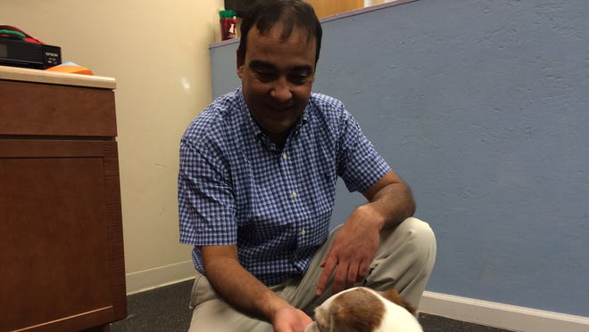Anil Regmi, veterinarian and owner of Urban Pet Hospital & Resort, gives a dog a Pet Dental Chew.