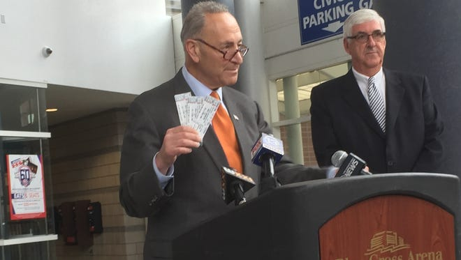 Sen. Charles Schumer, D-N.Y., holds images of actual tickets in talking about his legislation that would block bots from gobbling up and reselling tickets. John Parkhurst of the Rochester Broadway Theatre League is at right.