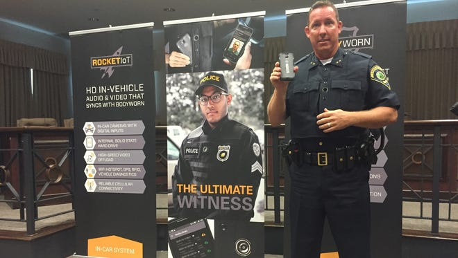 Lawrence Police Chief David Hofmann demonstrates the department's new body cameras.