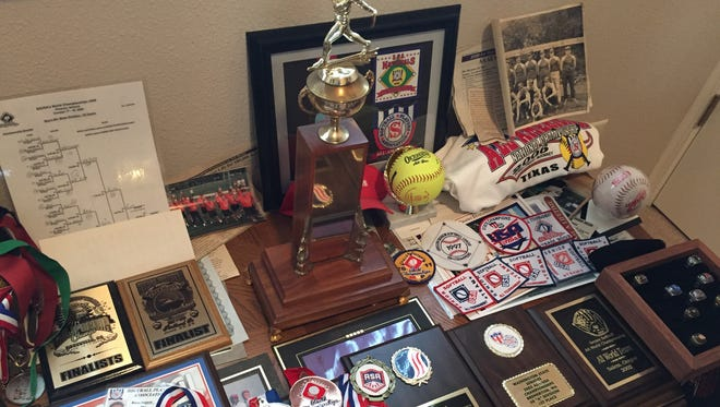 A collection of championship rings, tophies, plaques, medals, patches and team photos decorate a study in Jerry Bergquist's West Salem home.