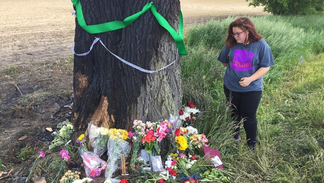 Burlington High School student Shelby Spencer-Horton on Tuesday visits the roadside memorial for three young men killed in fatal crash Sunday.