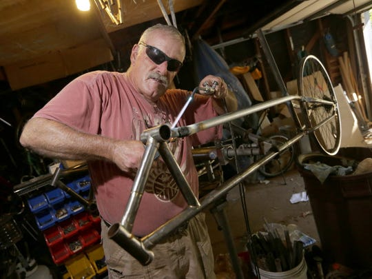 A.D. Carson, who runs Recycled Recumbents, uses a braising torch to put a frame together as he works on building a recumbent bike in his Glendale garage. Carson, a former theater-stage manager, chops up bicycles and makes them into recumbents. He has sold recumbents all over the U.S. and some abroad, all made in his garage.