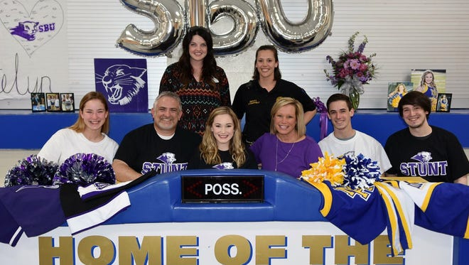 Mountain Home's Katelyn Mahan (first row, third from left) signed a letter of intent Monday at MHHS to be a member of the cheer team at Southwest Baptist University in Bolivar, Mo. Shown with Mahan at her ceremony are: (first row, from left) her sister, Kamryn Mahan, her father, Brook Mahan, her mother, Keri Mahan, her brother, Addison Mahan, her brother, Austin Mahan; (second row) MHHS varsity cheer coach Haley Mattick, and competitive cheer coach Danielle Campfield.