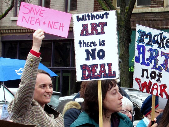 Arts supporters hold up signs at a rally Tuesday in Corning protesting proposed cuts in federal funding.