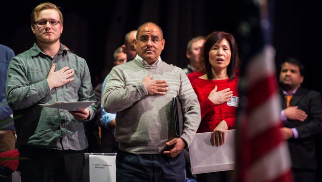 Benjamin Padraig Christian Carstens, formerly of Ireland, from left, Pablo Castellanos Hernandez, formerly of Mexico, and Ru Chen, formerly of the People's Republic of China, recite the Pledge of Allegiance after being naturalized during a ceremony for 55 new American citizens at Burlington High School in Burlington on Thursday, February 11, 2016.