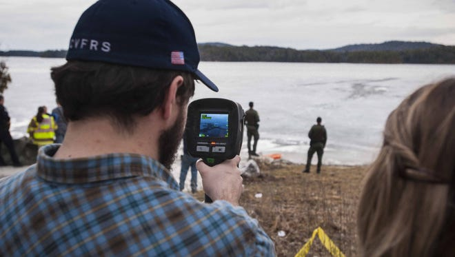 FILE: A member of the Charlotte Volunteer Fire and Rescue Squad uses a thermal imaging camera at Shelburne Pond in Shelburne on Wednesday, March 9, 2016, after a Fish and Game warden went through the ice while investigating a hole in the ice.