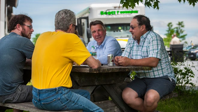 Republican candidate for governor Lt. Gov.r Phil Scott, center, chats with employees during a campaign visit at Maple Landmark Woodcraft in Middlebury on Wednesday, June 1, 2016.