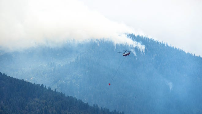 A helicopter carries a bucket while fighting the Hayden Pass Fire near Coaldale, Colo., on Monday, July 11, 2016.
