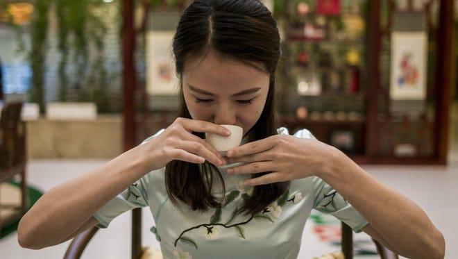 A hostess drinks tea during a tea ceremony.