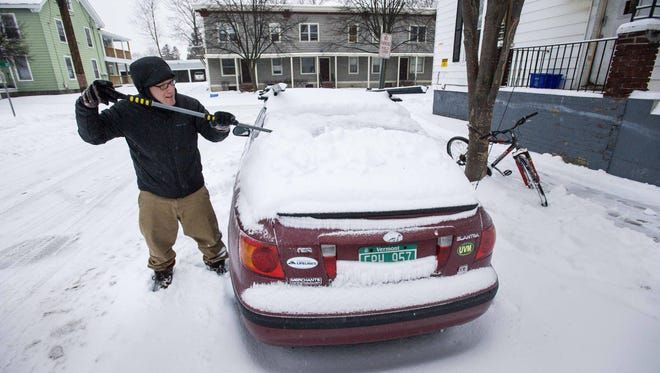"Jon Ayers clears snow from his car on  Clarke Street in Burlington on Tuesday, December 29, 2015. Said Ayers of the snow, ""I don't mind it at all. You just have to stay ahead of it. """