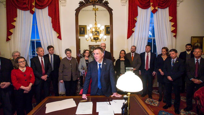 Governor Phil Scott signs several executive orders after swearing members of his cabinet at the Statehouse in Montpelier on Thursday, January 5, 2017