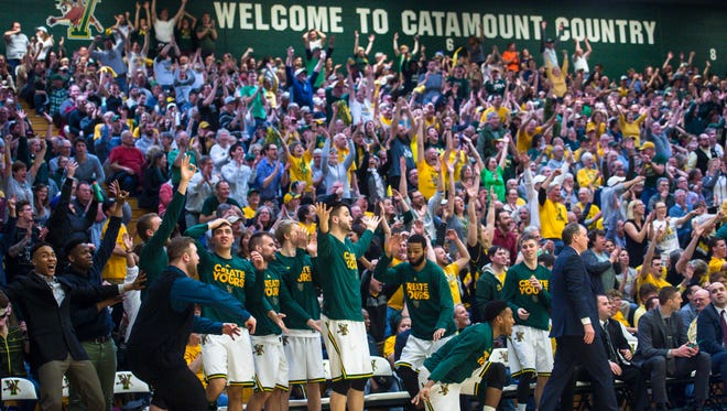 University of Vermont fans celebrate a three-point shot against the University of New Hampshire in Burlington on Monday, March 6, 2017.