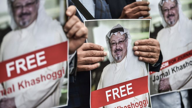 Protesters hold pictures of missing journalist Jamal Khashoggi during a demonstration Oct. 8, 2018, in front of the Saudi Consulate in Istanbul.