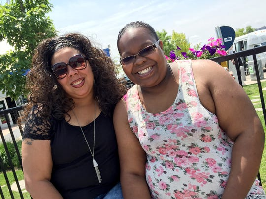 Nicole Thomas, 39, of Camp Springs, Md., and her cousin, Bertrina Stovall, 32, of Detroit, relax with their families on Detroit's RiverWalk Friday, July 10, 2015. Both women say posting humiliating videos to social media is not a good parenting strategy.