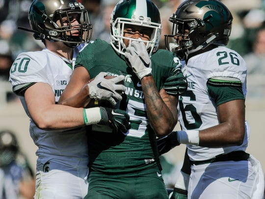Sean Harrington, left, and Brandon Randle, right, move in to tackle Darrell Stewart Jr. but the whistle was blown before they took Stewart down during the 2017 Green & White football game, Saturday, April 1, 2017, at Spartan Stadium in East Lansing.