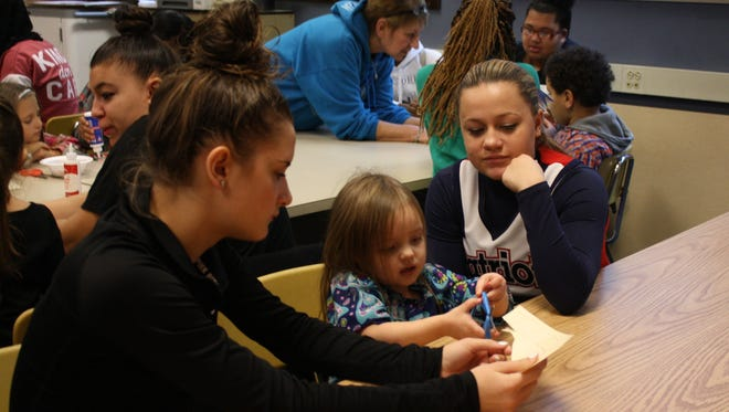 From left: Lexi Gruss, Khloe Spencer, and Ariana Taylor cut out a paper stocking during a Child Development class at Binghamton High School on Dec. 13.