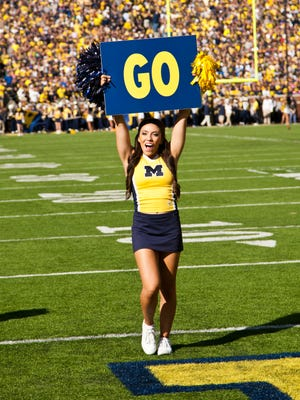 A Michigan cheerleader holds up a sign at Michigan Stadium on Oct. 10, 2015.